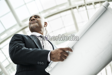 a black businessman holding plans for