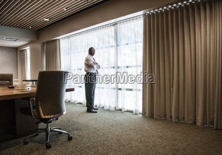 black businessman standing at a window
