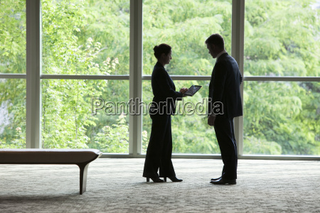 caucasian businessman and woman looking at
