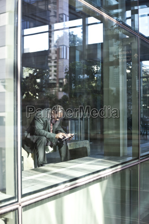 black business man texting while sitting