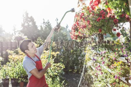caucasian man employee watering plants at