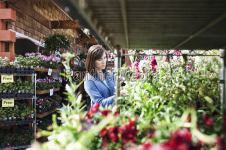 caucasian woman checking on plants in