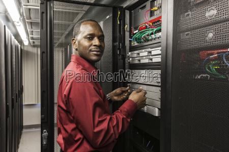 black man technician working on computer