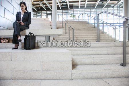 hispanic businesswoman sitting on stairs in