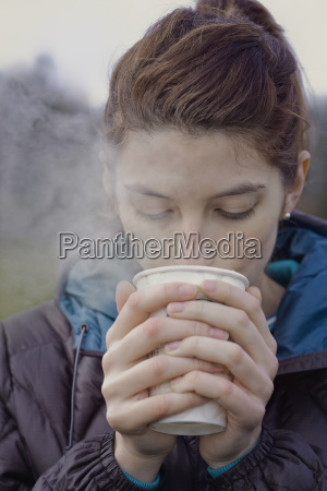 caucasian woman drinking a hot cup