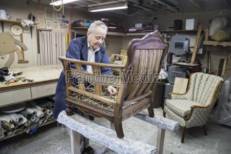 senior caucasian man upholsterer working on