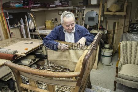 caucasian senior male upholsterer working on
