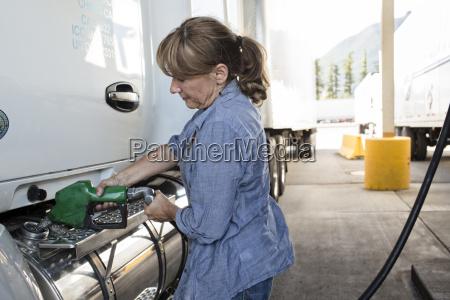 caucasian woman truck driver filling truck