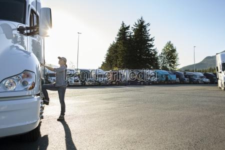 caucasian female truck driver getting into
