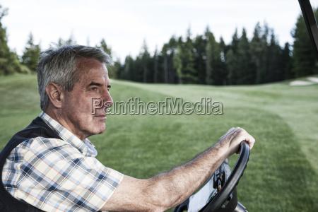 senior golfer driving a golf cart