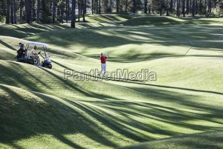 senior golfer hitting a second shot