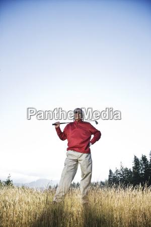 senior golfer standing in heavy rough