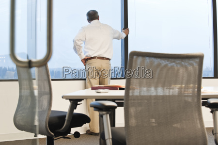 businessman standing at a window before