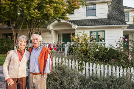hispanic senior couple in front of