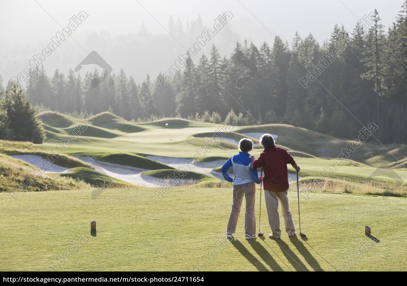 senior, golfing, couple, surveying, the, next - 24711654