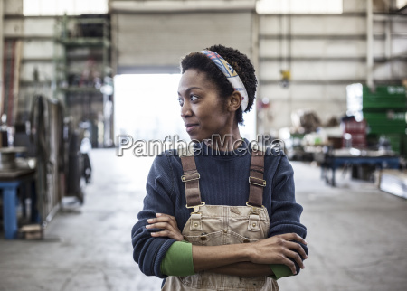 black woman factory worker wearing coveralls