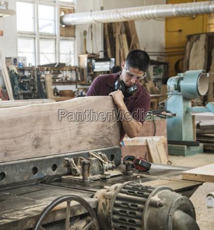 caucasian man factory worker cutting a