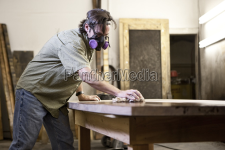 caucasian man factory worker applying finish