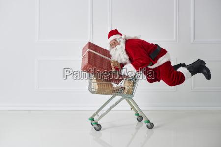 weihnachtsmann mit weihnachtsgeschenken mit einkaufswagen