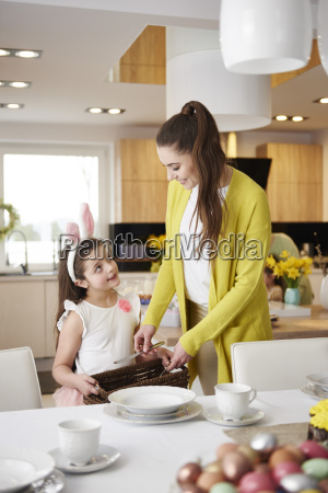 smiling mother and daughter setting the