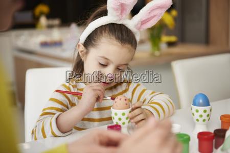 maedchen mit kaninchen sitzen am tisch