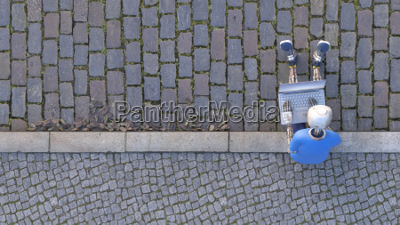 robot sitting on curb using laptop