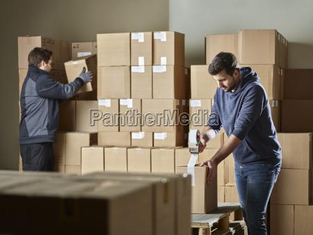 arbeiter die pakete mit paketband schliessen