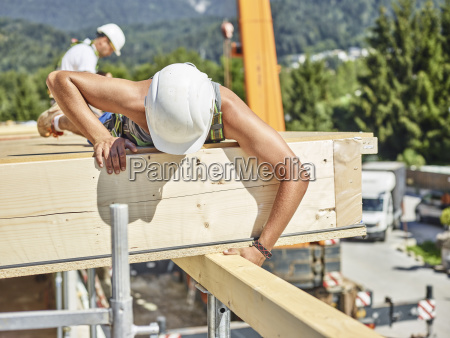 austria worker checking roof construction