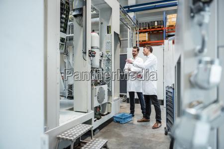 two men wearing lab coats talking
