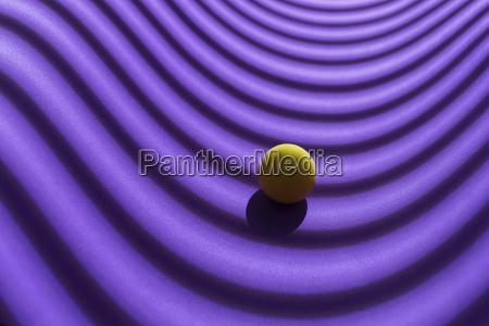 gelbe kugel ueber einem geometrischen violetten