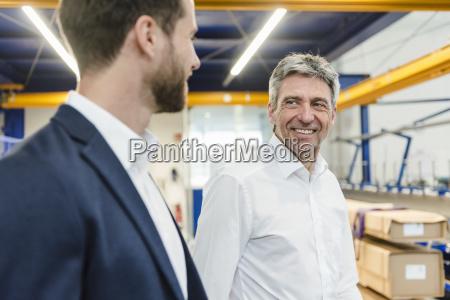unternehmer bei treffen in der produktionshalle