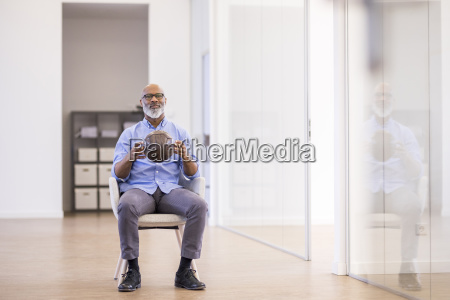 businessman with leather ball sitting on