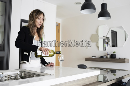woman serving wine in a glass