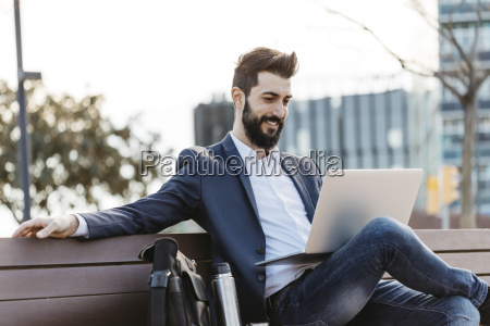 businessman sitting on bench outside office