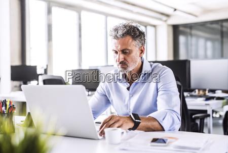 reifer geschaeftsmann sitzt mit laptop am