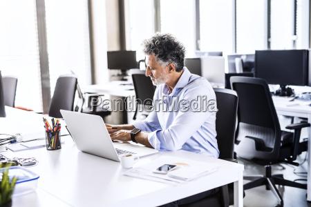 mature businessman working at desk in