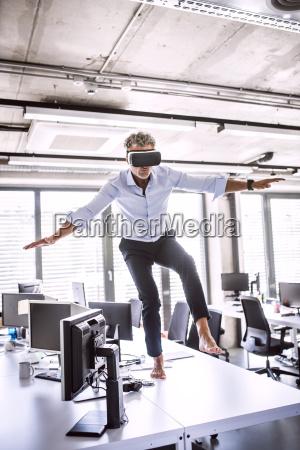 barefoot mature businessman on desk in