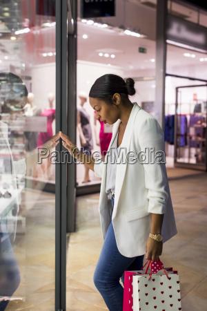woman looking in shop window of