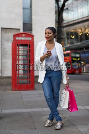 großbritannien, london, lächelnde, frau, mit, handy, das, einkaufstaschen, in - 24722514