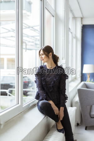 woman sitting at the window looking