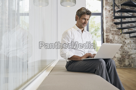 businessman sitting on bench in modern