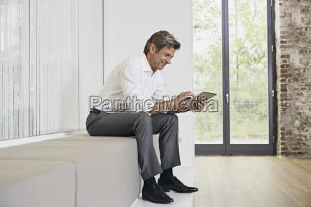 businessman sitting on bench in modern