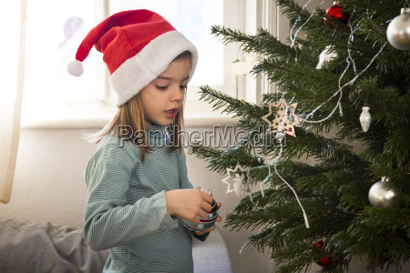 little girl wearing christmas cap decorating