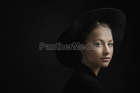 portrait of young woman against black