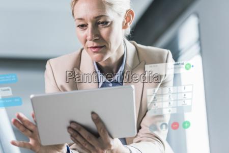 geschaeftsfrau sitzt im buero mit digitalem