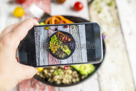 girl taking photo of vegan lunch