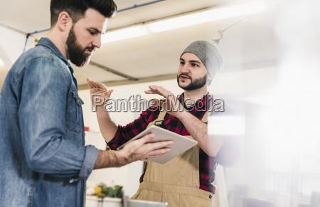zwei maenner mit tablet diskutieren im