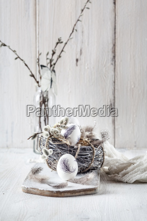 painted easter eggs nest feathers and