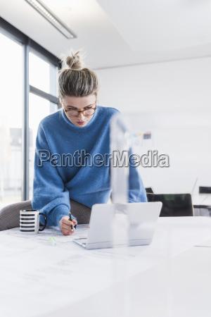 junge frau mit laptop und plan