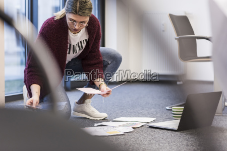 young woman with laptop and documents